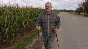 El caminante con los bastones acerca al campo de maíz almacen de metraje de vídeo