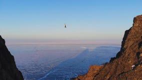 El caminante de la cuerda tirante se coloca en una honda y coge la balanza en la mucha altitud sobre el lago Baikal congelado metrajes