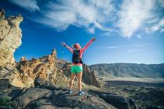 El caminante de la mujer con los brazos extendidos goza de las montañas fotos de archivo