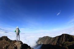 El caminante de la mujer en el balanceo hermoso se nubla el pico de montaña Imagen de archivo