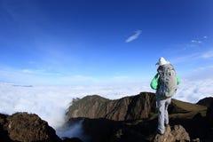 El caminante de la mujer en el balanceo hermoso se nubla el pico de montaña Imágenes de archivo libres de regalías
