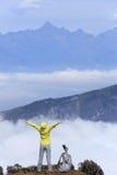 El caminante de la mujer en el balanceo hermoso se nubla el pico de montaña Fotos de archivo libres de regalías
