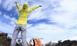 El caminante de la mujer en el balanceo hermoso se nubla el pico de montaña Imagen de archivo libre de regalías