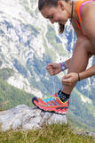 El caminante de la mujer joven que ata la bota ata, arriba en las montañas imágenes de archivo libres de regalías