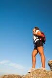 El caminante de la mujer se coloca en roca de la montaña Imagen de archivo