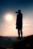 El caminante delgado en pantalones en el acantilado agudo del imperio de la roca está mirando abajo al valle de la mañana Sun cal Foto de archivo