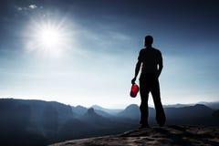 El caminante en casquillo rojo en el pico de la roca en imperios de la roca parquea y vigilando el valle brumoso y de niebla de l Imagenes de archivo