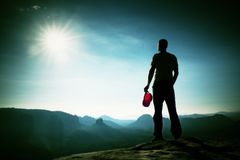 El caminante en casquillo rojo en el pico de la roca en imperios de la roca parquea y vigilando el valle brumoso y de niebla de l Imagen de archivo