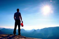 El caminante en casquillo rojo en el pico de la roca en imperios de la roca parquea y vigilando el valle brumoso y de niebla de l Fotos de archivo libres de regalías