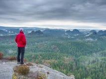 El caminante en la chaqueta roja ascendente hasta pico disfruta de la visión Escalador de montaña Imágenes de archivo libres de regalías