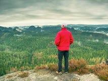 El caminante en la chaqueta roja ascendente hasta pico disfruta de la visión Escalador de montaña Fotografía de archivo