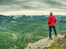 El caminante en la chaqueta roja ascendente hasta pico disfruta de la visión Escalador de montaña Imagen de archivo libre de regalías