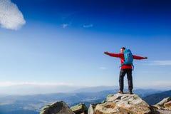 El caminante en la cima de una roca con la mochila disfruta de día soleado Foto de archivo libre de regalías