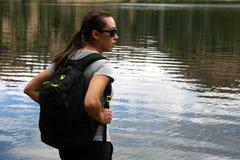 El caminante en las montañas descansa en un lago Imágenes de archivo libres de regalías