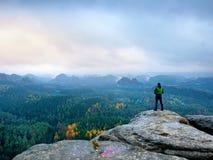 El caminante en windcheater verde, el casquillo y los pantalones oscuros del senderismo se colocan en roca del pico de montaña Foto de archivo