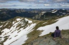 El caminante femenino admite la visión en la cima de una montaña nevosa Foto de archivo libre de regalías