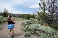 El caminante femenino camina en una pista de senderismo de la suciedad en mineros encanta Wyoming para explorar un pueblo fantasm imágenes de archivo libres de regalías