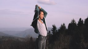 El caminante femenino joven se está colocando de aumento de las manos en el borde del canto de la montaña contra el fondo del c metrajes