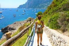 El caminante femenino va abajo y pendiente el camino con el paisaje espectacular de Capri, Nápoles, Italia Imágenes de archivo libres de regalías