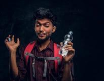 El caminante indio con la mochila consiguió una sensación de revolvimiento bebió un sorbo de agua dulce Foto del estudio contra u foto de archivo