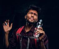 El caminante indio con la mochila consiguió una sensación de revolvimiento bebió un sorbo de agua dulce Foto del estudio contra u fotografía de archivo libre de regalías
