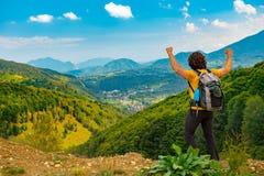 El caminante joven de la montaña con los brazos aumentó para arriba, celebrando y disfrutando de un paisaje hermoso de la montaña imagen de archivo