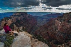 El caminante que mira abajo del cabo real pasa por alto Grand Canyon Rim Wo del norte Foto de archivo libre de regalías
