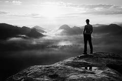 El caminante solo en la camisa blanca y el casquillo rojo se colocan en el pico de la roca en imperios de la roca parquean y vigi Fotos de archivo