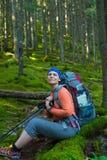 El caminante sonriente de la mujer con la mochila es relajante en FO coníferas Imagen de archivo