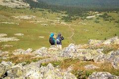 El caminante y el fotógrafo permanecen en un soporte rocoso Foto de archivo