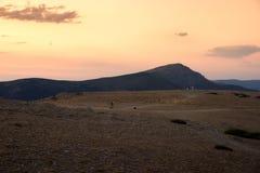 El caminante y su perro caminan abajo de la montaña en una puesta del sol asombrosa Fotos de archivo