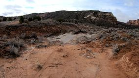 El caminar abajo de una trayectoria roja de la suciedad cerca del monumento nacional de Colorado metrajes