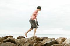El caminar adolescente descalzo en rocas de la playa Foto de archivo libre de regalías