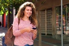 El caminar adolescente feliz en la acera con los auriculares y el móvil Foto de archivo
