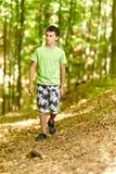 El caminar adolescente a través de un bosque fotos de archivo libres de regalías