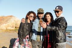 El caminar africano feliz de los amigos hace el selfie por el teléfono móvil fotografía de archivo