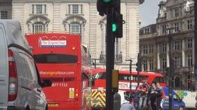 El caminar apretado ciudad de los autobuses y de la gente del autobús de dos pisos de los semáforos de la calle de Londres