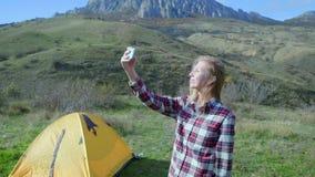 El caminar atractivo de la muchacha hace el selfie en smartphone en un fondo de montañas Una muchacha se coloca cerca de la tiend almacen de video
