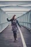 El caminar bonito de la muchacha feliz en un puente Fotografía de archivo libre de regalías