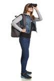 Caminante de la muchacha con la mochila que mira a través de los prismáticos Imagen de archivo libre de regalías