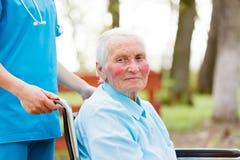 El caminar con una señora mayor en silla de ruedas Imagen de archivo libre de regalías