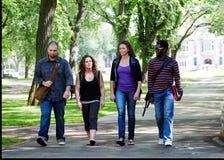 El caminar de cuatro estudiantes universitarios Foto de archivo