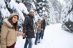 El caminar de Forest Happy Smiling Young People de la nieve del grupo de los amigos al aire libre Fotos de archivo libres de regalías