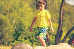El caminar de funcionamiento del muchacho al aire libre Imagenes de archivo