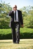 El caminar de Hearing Wearing Sunglasses del guardia de seguridad imagenes de archivo