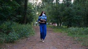 El caminar de la madre y del niño jovenes en sus manos en el bosque - cámara lenta almacen de video