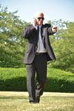 El caminar de Pointing Wearing Sunglasses del guardia de directivo de seguridad foto de archivo