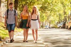 El caminar de tres amigos de las personas al aire libre Foto de archivo libre de regalías