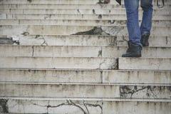 El caminar del hombre sube para arriba en escaleras viejas Fotografía de archivo