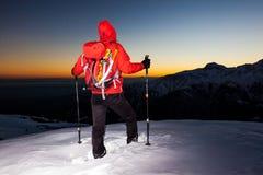 El caminar del invierno: el hombre se coloca en un canto nevoso que mira la puesta del sol Fotos de archivo